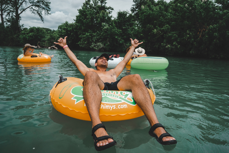 Guy floating on the san marcos river